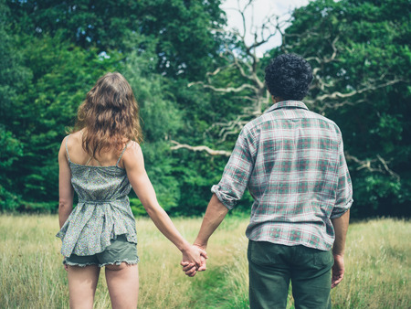 endearment: A young couple is standing in a meadow in the forest and holding hands Stock Photo