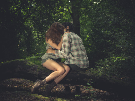 endearment: A young couple is sitting on a log in the forest and kissing