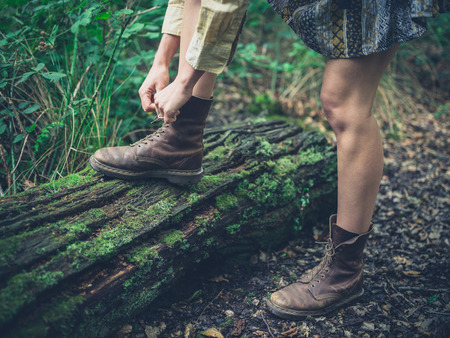 walking boots: A young woman is tying the laces of her walking boots on a log in the forest Stock Photo