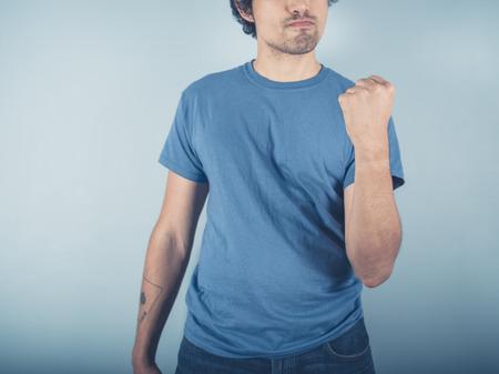 fist pump: A confident young man wearing a blue t-shirt is doing a fist pump