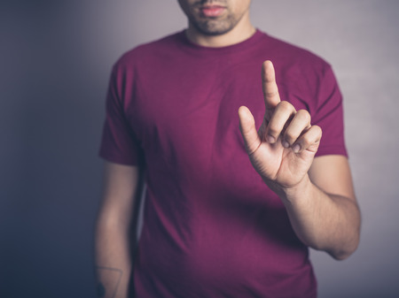 swipe: A young man in purple is raising his finger to swipe, push or establish authority