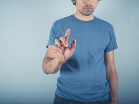 swipe: A young man wearing a blue t-shirt is raising his finger to either point or swipe or push