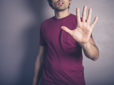 human palm: A young man wearing purple is raising his open hand to signal stop