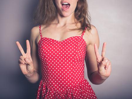 donna sexy: Una giovane donna in un bel vestito rosso sta visualizzando la V di vittoria segno e sorride Archivio Fotografico