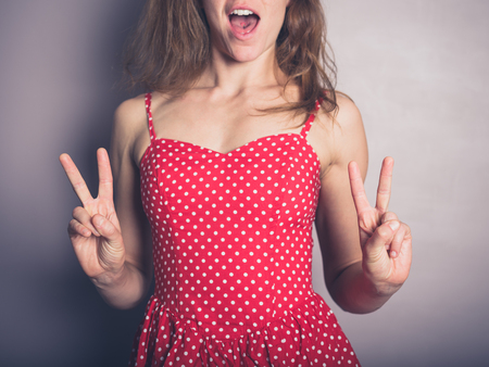 A young woman in a pretty red dress is displaying the v for victory sign and is smiling