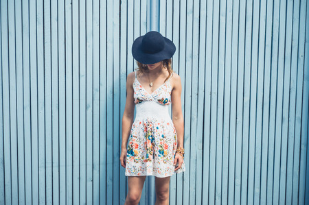 A young woman wearing a summer dress with a hat is standing outside by a blue fence