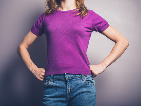 woman hands: A confident young woman in purple shirt is standing in a powerful pose with her hands on her hips