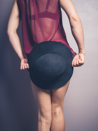 cover up: A young woman wearing seductive lingerie is holding a hat to cover up her behind