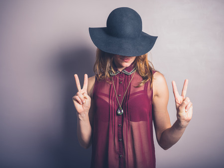 A sexy and fashionable lady wearing a hat and a see through shirt is showing the v sign