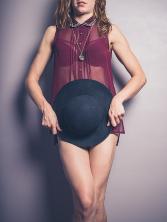 modesty: A seductive young woman wearing see through lingerie is covering her modesty with a hat Stock Photo