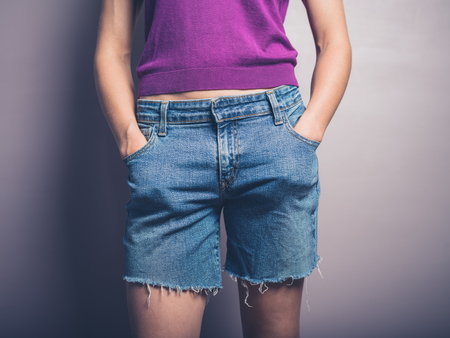 denim shorts: A young woman wearing denim shorts is posing with her hands in her pockets