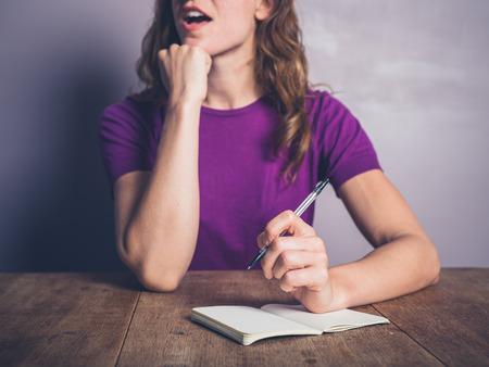 Een doordachte jonge vrouw schrijft in een notitieblok op een tafel Stockfoto - 45151544