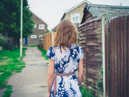 neighbourhood: A young woman wearing a dress is walking in a residential neighbourhood