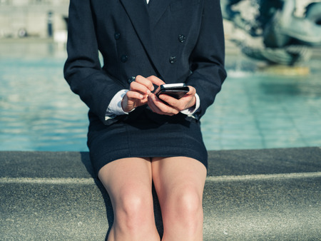 busineswoman: A young busineswoman is sitting by a fountain in the city and is using a smart phone Stock Photo