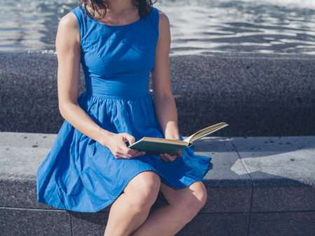 beauty fountain: A young woman wearing a blue dress is sitting by a fountain in the city and is reading a book