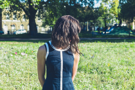unrecognisable people: A young woman is standing in a meadow on a sunny day