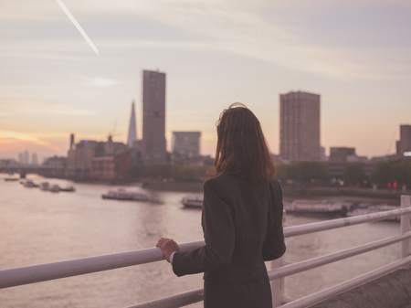 young business: A young businesswoman is standing on a bridge at sunrise and is admiring the London skyline