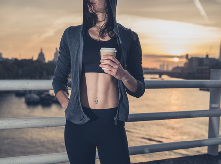 An athletic young woman with toned abs  is standing on a bridge in London at sunrise with a paper cup in her hand
