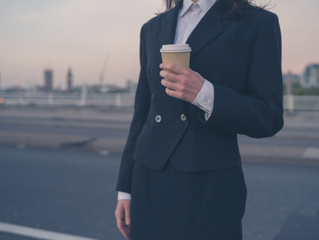paper cup: A young businesswoman is standing in the road at sunrise with a paper cup in her hand Stock Photo