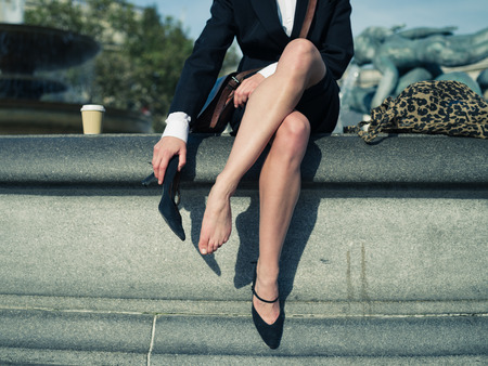 A young businesswoman is sitting on a the edge of a fountain in a city and is taking off her shoe to rest her foot
