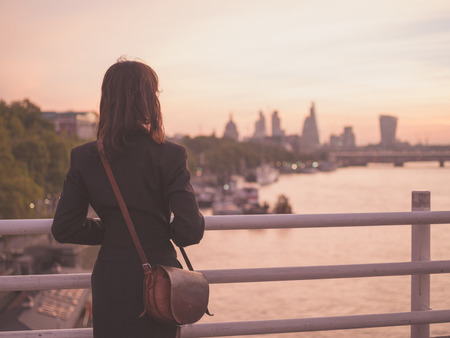 city of sunrise: A young woman with a shoulderbag is standing on a bridge and is admiring the sunrise over the London skyline Stock Photo
