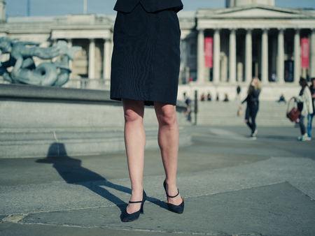 business woman legs: The legs of a young businesswoman wearing heels and a skirt standing in a square in the city on a sunny day