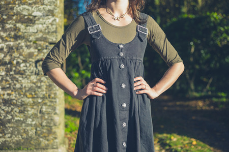 hand on hip: A confident young woman is standing in the countryside with her hands on her hips