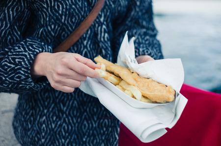 comida inglesa: Una mujer joven est� sentado fuera y est� comiendo pescado y patatas fritas