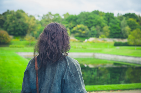 formal garden: A young woman is exploring a formal garden with a small pond Stock Photo
