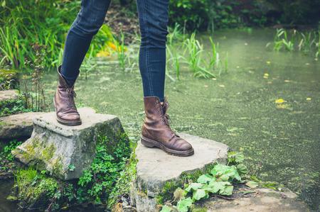 小さな池の飛び石を渡ってトレッキングタッチ若い人の足 写真素材
