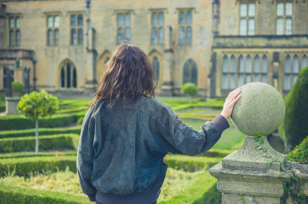 stately home: A young woman is exploring a formal garden and stately home