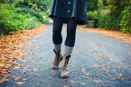 calcetines: Las piernas de una mujer joven con los calcetines a rayas y botas ya que es caminar en un camino rural en el oto�o Foto de archivo