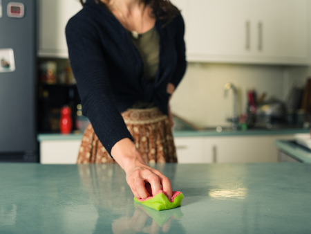 scrubbing: A young woman is scrubbing and cleaning the worktop in her kitchen with a sponge Stock Photo