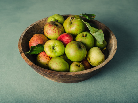 green apples: A bowl of freshly picked green apples on a green table