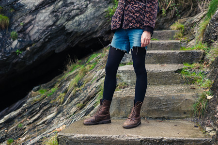 concrete steps: A young woman wearing hiking boots is standing on some concrete steps outdoors amongst the rocks