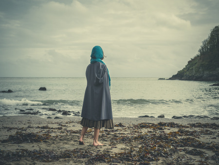 A young barefoot woman wearing a headscarf is standing on a beach on a cold and windy day