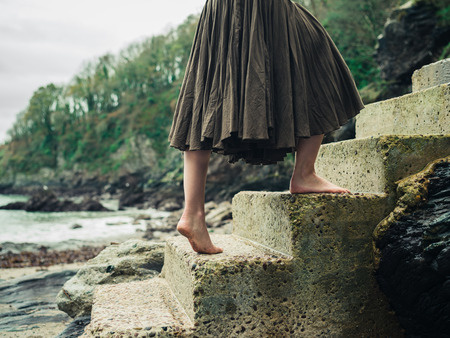 concrete steps: The feet of a young barefoot woman as she is walking up some concrete steps in nature Stock Photo