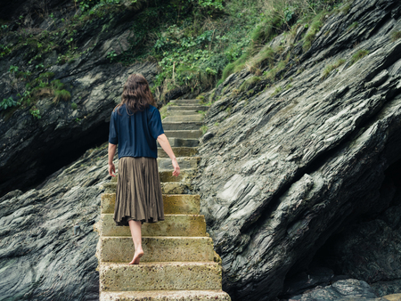 woman barefoot: A young barefoot woman is walking on some stairs leading up a cliff