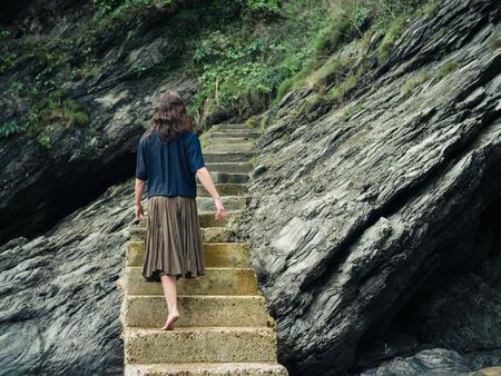 pies descalzos: Una mujer descalza joven está caminando en unas escaleras que conducen un acantilado Foto de archivo