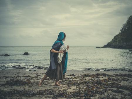 아기를 쥐고 해변에 젊은 여자의 극적인 빈티지 필터링 개념 쐈 어 담요에 tighly를 싸서