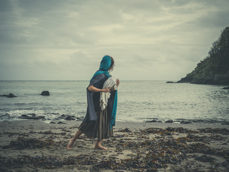 mother of jesus: Dramatic vintage filtered concept shot of a young woman on a beach clutching a baby wrapped up tighly in a blanket Stock Photo