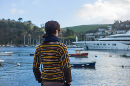 super yacht: A young woman is standing in a harbour and is looking at the boats moored there including a grand and luxurious super yacht