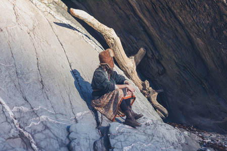 large rock: A young woman is sitting an drelaxing on a large rock in nature at sunset