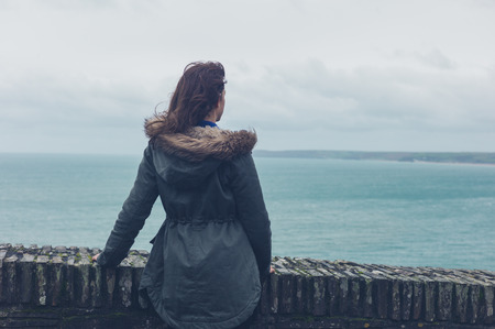 person: A young woman wearing a winter coat is standing by the sea Stock Photo