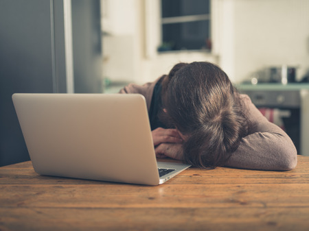 A sad young woman is sleeping by her laptop in her kitchen at home