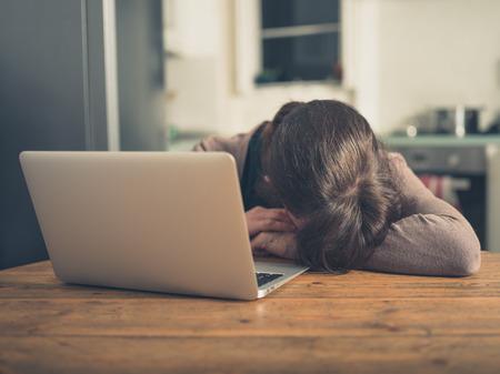 Una giovane donna triste sta dormendo dal suo computer portatile nella sua cucina a casa Archivio Fotografico