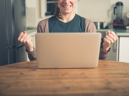 fist pump: A young woman is using her laptop in a domestic kitchen and is doing a double  fist pump as she is getting excited