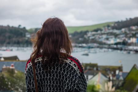 women thinking: Una mujer joven est� de pie en la cima de una colina y me slooking en un estuario con los barcos Foto de archivo