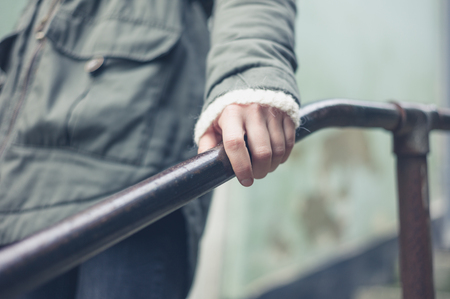 banister: The hand of a woman holding on to a metal banister outside Stock Photo
