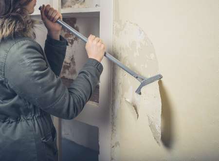 stripping: A young woman wearing a warm winter coat is renovating a house and is stripping off the wallpaper Stock Photo
